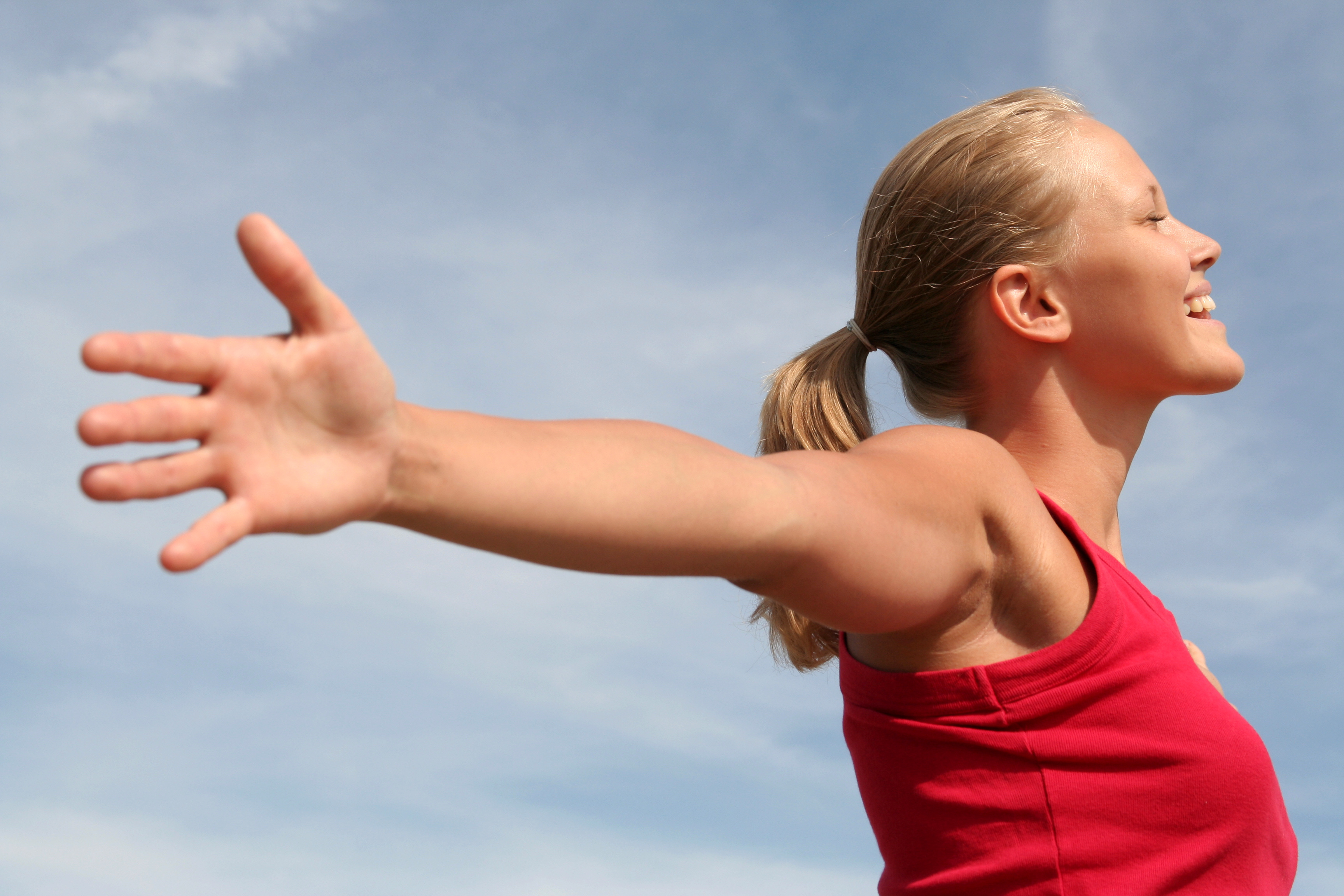 happy young woman with arms outstretched